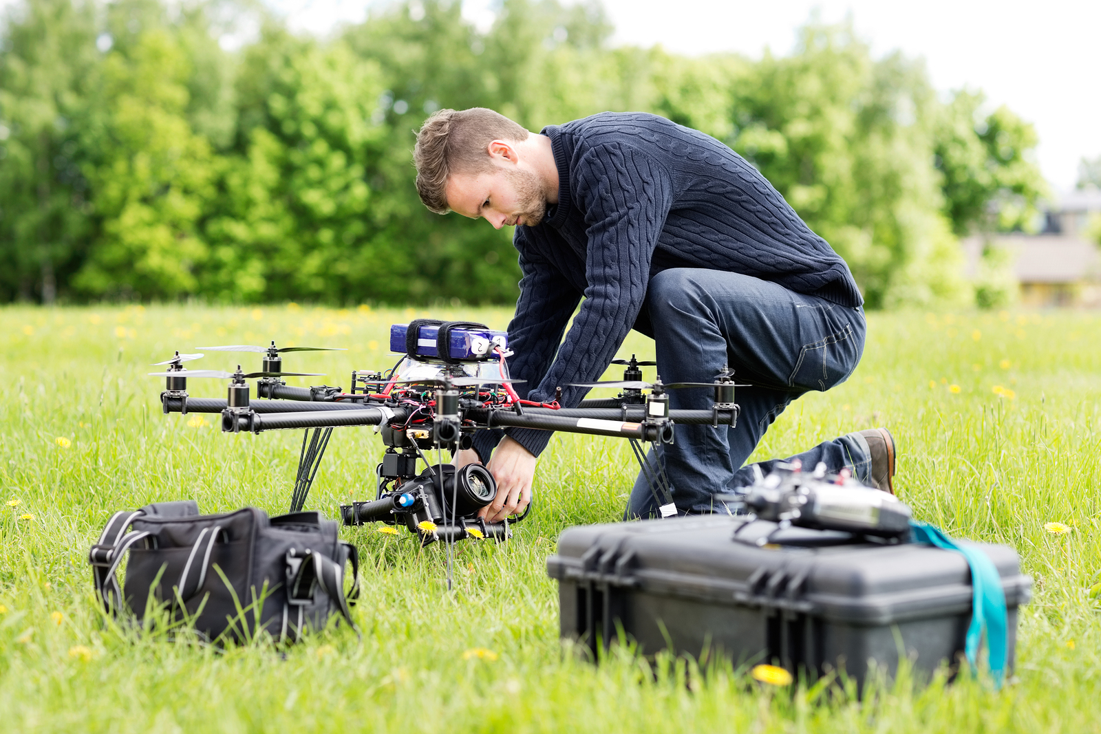 Young engineer setting SLR camera on UAV helicopter at park